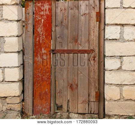 Wooden door with old door lock brick wall.