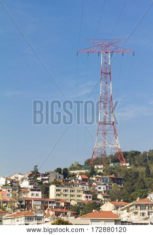 Electric smog. High voltage electricity pylon and power line above a residential area.