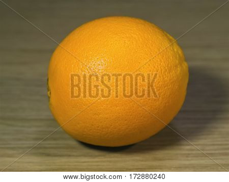 The fresh orange on a wooden surface
