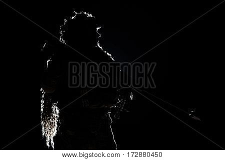Army sniper with big rifle standing on black background. Backlit contour silhouette shot. Invisible death concept