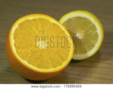 The orange and lemon on a wooden surface closeup