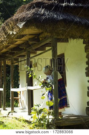 Lvov, Ukraine - June 24, 2016: Old wooden house under thatched roof with old woman in flowered ethnic dress reading book in corner of house in distance on village