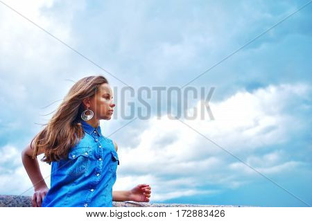 Wonderful portrait of a cute slender girl with a beautiful profile with long hair fluttering with the wind on blue sky background with moving clouds close-up