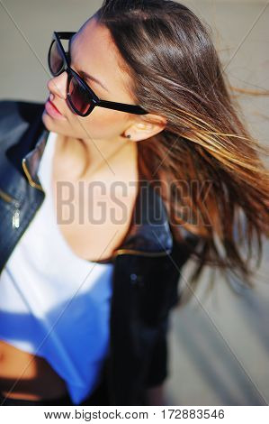 Wonderful portrait of a young attractive girl in sunglasses with long hair fluttering with the wind on gray background blurred focus close-up.