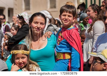 Happy Jewish Family Celebrate The Purim Holiday At Street Event
