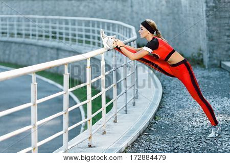 Sport, exercises outdoors. Girl in orange and black training suit doing stretching on stadium. One leg on crossbar, stretching leg. Full body, profile