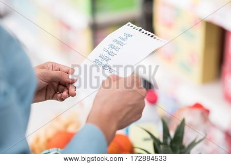 Woman doing grocery shopping at the supermarket she is pushing a full shopping cart and checking a list