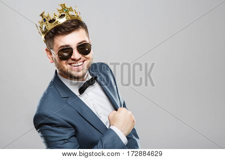 Stylish young man in suit with bow and sunglasses. Wearing crown. Bended ahead, smiling. Outrageous, fancy look. Waist up, studio, indoors