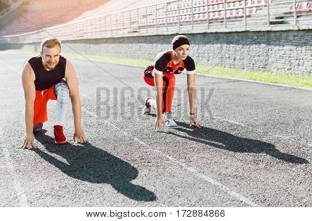 Sport, exercises outdoors. Man and woman in orange and black training suits standing on start position. Before running on stadium. Full body, looking ahead, concentrated