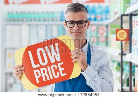 Supermarket Clerk Holding A Sign