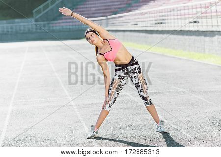Sport, exercises outdoors. Girl in rose top and black and white leggins doing stretching on stadium. Bending aside. Full body, looking aside