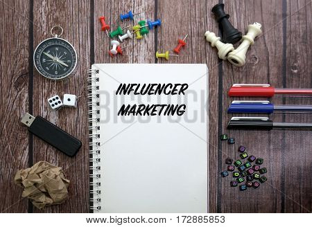INFLUENCER MARKETING CONCEPT ON NOTEBOOK WITH STATIONERY