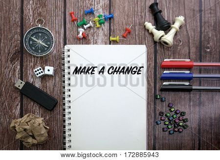 MAKE A CHANGE CONCEPT ON NOTEBOOK WITH STATIONERY