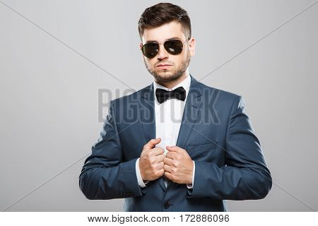 Stylish young man in suit with bow and sunglasses. Looking at camera, hands on jacket. Jacket, bow, official outlook. Waist up, studio, indoors