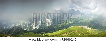 Deep hanging clouds above mountains and valley. Mystic light breaks through the fog.