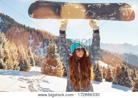 Girl Snowboarder Standing On A Mountain Top Keeps, Snowboard Over The Head