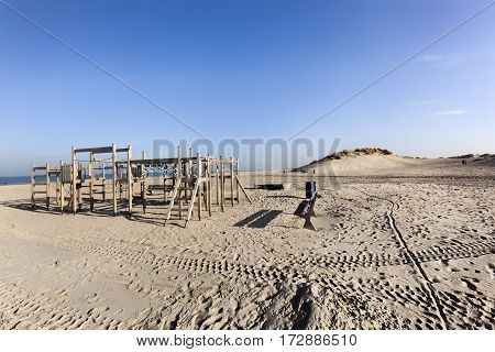 Wooden playground on the beach of Hoek van Holland in the Netherlands with some dunes in the background