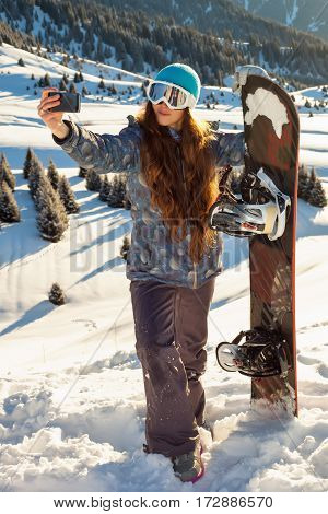 Girl Snowboarder Standing On A Mountain Top At Sunset And Making A Selfie