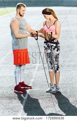 Sport, exercises with expander outdoors. Coach in bright orange shorts explains to girl in rose top and black and white leggins how to do exercises with expander right. Full body, stadium