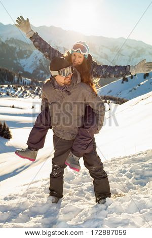Smiling Snowboarder Holding Girlfriend On His Back