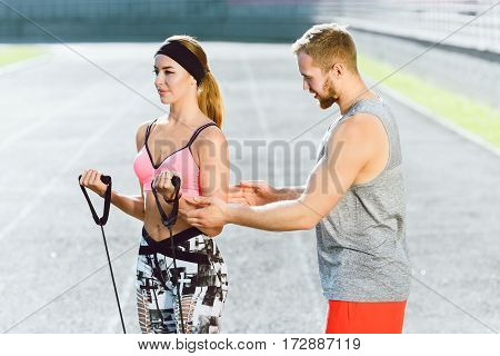 Sport, exercises with expander outdoors on stadium. Coach in bright orange shorts explains to girl in rose top and black and white leggins how to do exercises with expander right