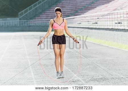 Sport, exercises outdoors. Girl in rose top and black shorts jumping on skipping rope on stadium. Sporty girl in good shape, full body, looking down