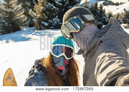 Couple Snowboarder Standing On A Mountain Top At Sunset And Making A Selfie