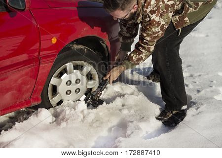 The man turns up shovel wheel of a car with snow drifts.  Difficult road conditions. Digging the car out of a snowbank shovel.