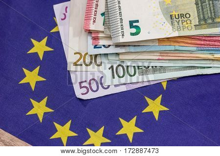 Euro Bills With Euro Flag On Desk.