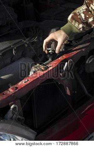 Checking the coolant level in the car.  The cap of the radiator, check fluid, replacement fluid.  Mechanic pouring coolant to the radiator.  Male lists the coolant in the cooling system.
