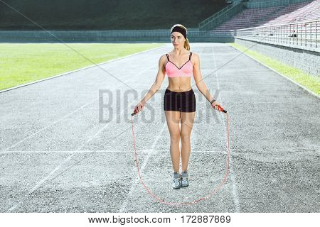 Sport, exercises outdoors. Girl in rose top and black shorts jumping on skipping rope on stadium. Sporty girl in good shape, full body, looking aside, outdoors