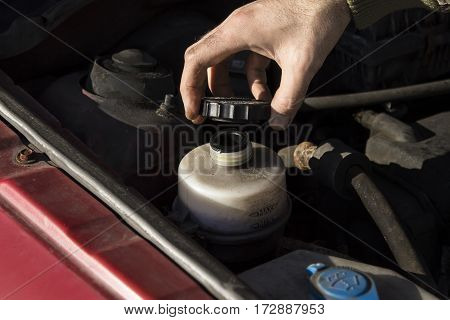 Steering fluid change.  The mechanic fills the tank power steering fluid.  Mechanic tightened the valve steering fluid reservoir. Car mechanic lists steering fluid.