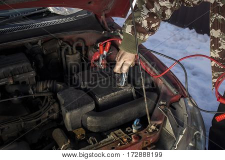 Mechanic jumper cables connected to a discharged battery. Firing the car in the winter by the jumper cables.