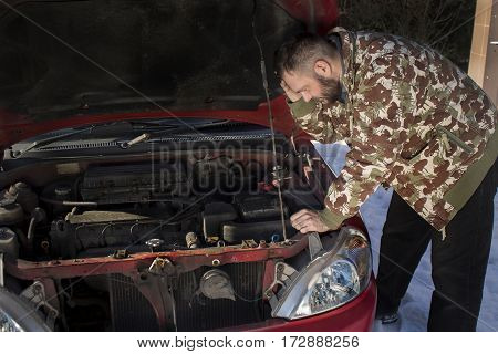 Mechanic wonders what went wrong in the car.  Helpless man looks at the spoiled engine in the car.