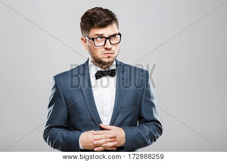 Stylish young man in suit with bow and eyeglasses. Fingers crossed, looking up with suspicion. Jacket, bow, official outlook. Waist up, studio, indoors
