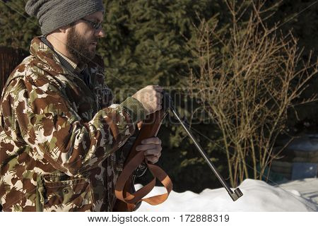 Man charged windbreaker in winter snow-covered forest. Man in winter forest reloads pneumatic weapons.  Hunter dressed in camouflage with pneumatic gun, rifle  The man in the white winter forest loads long arms.