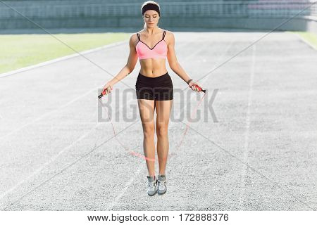 Sport, exercises outdoors. Girl in rose top and black shorts jumping on skipping rope on stadium. Sporty girl in good shape, full body, closeup, looking down, outdoors