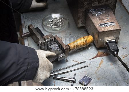 Craftsman plant produces components for the machines. Manufactory, manual manufacturing of lead alloy .An employee at the plant craft while working.