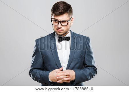 Stylish young man in suit with bow and eyeglasses. Fingers crossed, looking aside with contempt. Jacket, bow, official outlook. Waist up, studio, indoors