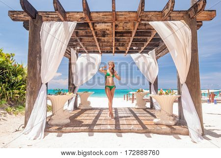 Woman at caribbean beach with pergola (gazebo) in Dominican Republic