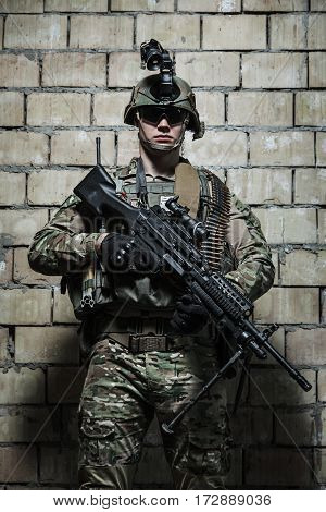 US Army Ranger with machinegun and night vision goggles standing near the wall. Front view portrait