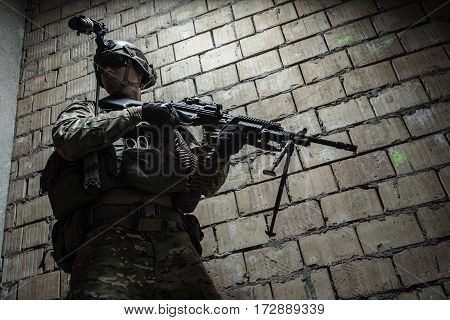 US Army Ranger with machinegun and night vision goggles moving along the wall during mission. Low angle view