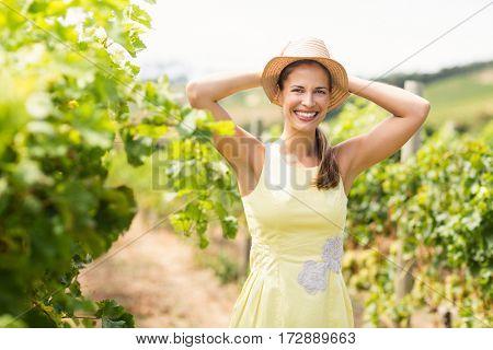 Portrait of female vintner in hat standing in vineyard