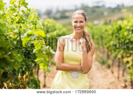 Portrait of smiling female vintner standing in vineyard