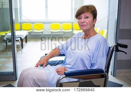Portrait of sad senior patient sitting on a wheelchair in hospital