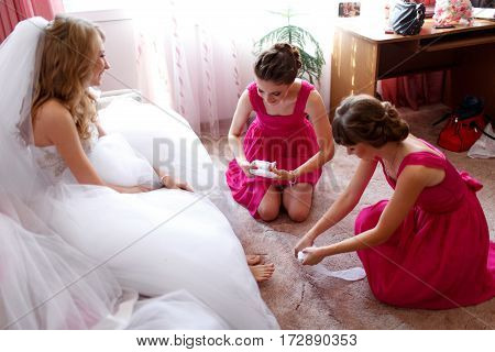 Bridesmaids in pink dresses help bride to put on a garter and stockings