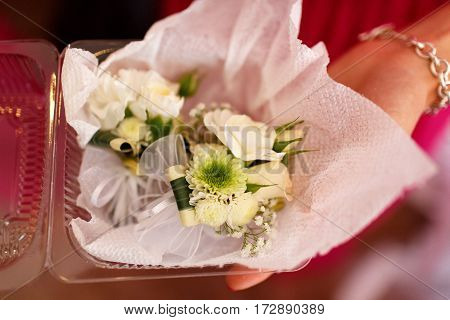 Lady holds a box with boutonniere made on roses in her arms