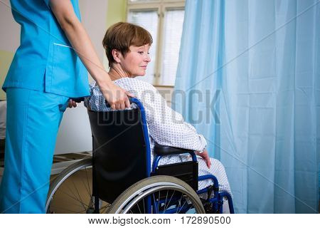 Patient sitting on wheel chair with nurse standing behind in hospital