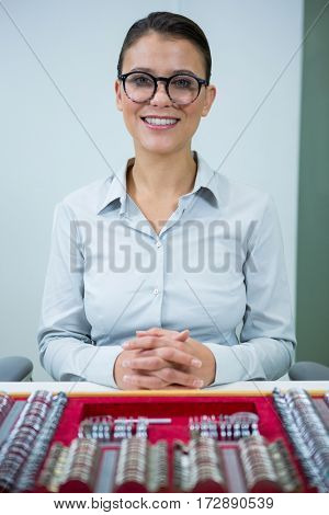 Portrait of smiling optician sitting with tool box on table in optical store