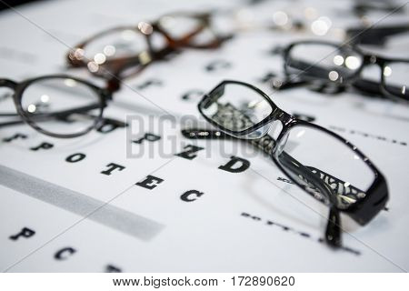 Close-up of various spectacles on eye chart in ophthalmology clinic